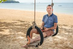 The man is sitting on a swing and relax. Lifestyle concept. Thailand, Krabi. February 2017. The man is sitting on a swing and relax. Lifestyle concept. Thailand Royalty Free Stock Photos