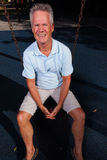 Man sitting on a swing. Senior man sitting on a park swing Royalty Free Stock Image