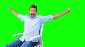 Man sitting on swivel chair with raised arms to show his success on green screen Royalty Free Stock Image