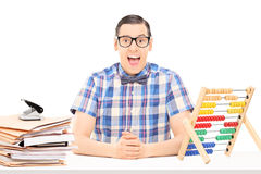 Man sitting on a table with abacus and a pile of documents Royalty Free Stock Images