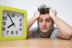 Man sitting at the table with big clock Stock Image