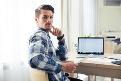Man sitting at the table and checking bills Stock Photos