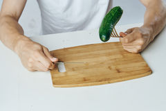Man sitting at a table, cucumber on a cutting board, white background.  Royalty Free Stock Photography