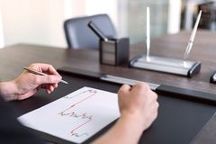 Man sitting at table and holds pen in his hand. There are sheet of paper with a trading chart on the table. Concept photo. royalty free stock photo