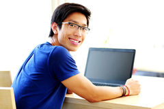 Man sitting at the table with laptop stock photography