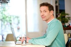 Man sitting at table with laptop Royalty Free Stock Photos