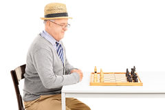 Man sitting at table and looking at a chessboard Stock Image