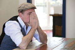 Man sitting at table looking tired Royalty Free Stock Photography
