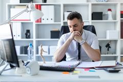A man is sitting at a table in the office and is looking at a wooden little man. A bearded man with a business suit is working in a bright office. photo with Royalty Free Stock Photos