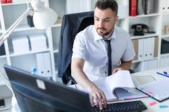 A man is sitting at a table in the office, working with documents and a computer. A bearded man with a business suit is working in a bright office. photo with Royalty Free Stock Image