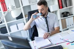 A man is sitting at a table in the office, working with documents and drinking water from a bottle. A bearded man with a business suit is working in a bright Royalty Free Stock Photography
