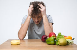 Man sitting at the table with vegetables Stock Image