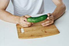 Man sitting at a table on a white background, cucumber, vegetables, cutting board, diet, vegetarianism.  Stock Image