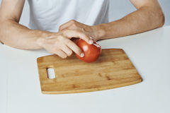 Man sitting at a table on a white background, tomato, cutting board, vegetables, diet, vegetarianism.  Stock Image