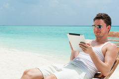 Man sitting with tablet on beach Stock Images