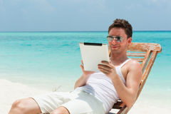 Man sitting with tablet on the beach with the sea, ocean view Stock Photos