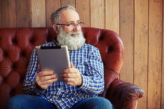 Man sitting with tablet pc with good mood. Bearded senior man sitting with tablet pc with good mood Stock Photography