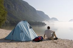 Man sitting beside a tent Royalty Free Stock Images