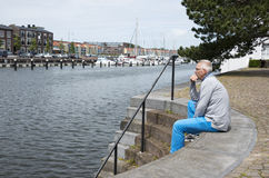 Man sitting and thinking near the water Stock Photos