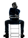 Man sitting  thinking pensive silhouette full length Stock Photos