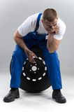 Man sitting on tire on grey background. Royalty Free Stock Photography
