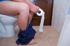 Man sitting on the toilet. Constipation or diarrhoea. Stock Images