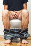 Man sitting on toilet Stock Photo