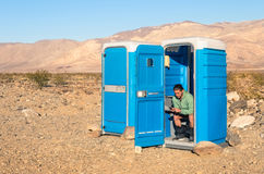 Man sitting in the Toilet in the middle of the desert - Death Va Stock Photo