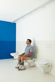 Man sitting on the toilet Royalty Free Stock Photo