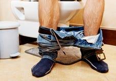 Man sitting on a toilet seat.  Royalty Free Stock Photos