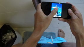 Man sitting on toilet using cell smart phone pov of guy watching photos. In bathroom stock video footage