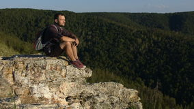 Man sitting on top of a cliff and looking into the camera and smiling. stock footage