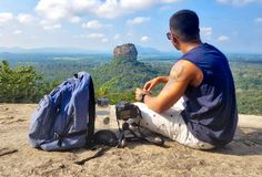 Man Sitting on Top of Gray Cliff Mountain Beside Backpack, Water Bottle, and Camera Royalty Free Stock Photo