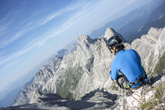 Man sitting on top of the mountain. With a beautiful view royalty free stock photography