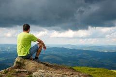 Man sitting on the peak of the mountain. Man sitting on the top of the mountain. Cloudy stock photos