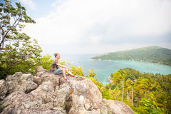 Man sitting on top of a mountain and enjoying view. Man sitting on top of a mountain and enjoying beautiful view stock photography