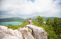 Man sitting on top of a mountain and enjoying view. Man sitting on top of a mountain and enjoying beautiful view royalty free stock image