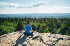 Man sitting on the top of the mountain in meditation session in Lotus Posture, padmasana, practicing pranayama