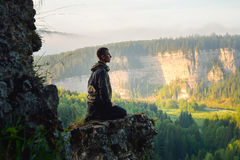 Man sitting on the top of the mountain and meeting sunrise Stock Photo