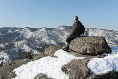 Man sitting at top of the mountain, Mountain Round, Altai, Russia. Man sitting at top of the mountain, Mountain Round, Belokurikha city, Altai, Russia royalty free stock photography