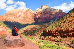 Man sitting on top of the mountain and resting. Beautiful red mountains scenery. Road on the bottom of the canyon. Zion National Park, Utah, USA stock photography