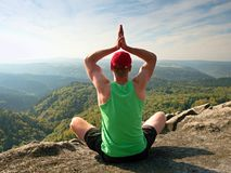 Man sitting on the top of the mountain in yoga pose. Exercise yoga on the edge with a breathtaking view. Of the landscape. Merging the soul with nature royalty free stock photos