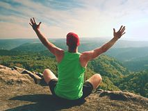 Man sitting on the top of the mountain in yoga pose. Exercise yoga on the edge with a breathtaking view. Of the landscape. Merging the soul with nature stock photo