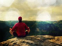 Man sitting on the top of the mountain in yoga pose. Exercise yoga on the edge with a breathtaking view. Lens defect. Man sitting on the top of the mountain in stock images