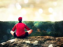 Man sitting on the top of the mountain in yoga pose. Exercise yoga on the edge with a breathtaking view. Lens defect. Man sitting on the top of the mountain in stock photos