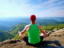 Man sitting on the top of the mountain in yoga pose. Exercise yoga on the edge with a breathtaking view. Of the landscape. Merging the soul with nature royalty free stock photography
