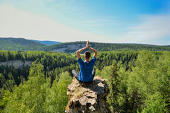Man sitting on the top of the mountain in yoga pose. Leisure in harmony with nature stock photo