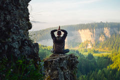 Man sitting on the top of the mountain in yoga pose. Leisure in harmony with nature royalty free stock images