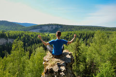 Man sitting on the top of the mountain in yoga pose. Leisure in harmony with nature stock photos
