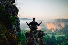 Man sitting on the top of the mountain in yoga pose. Meeting sunrise royalty free stock images